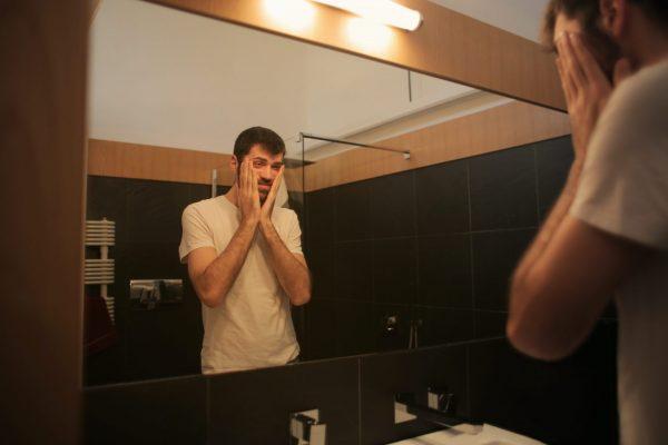 tired-man-looking-in-mirror-in-bathroom-3771135